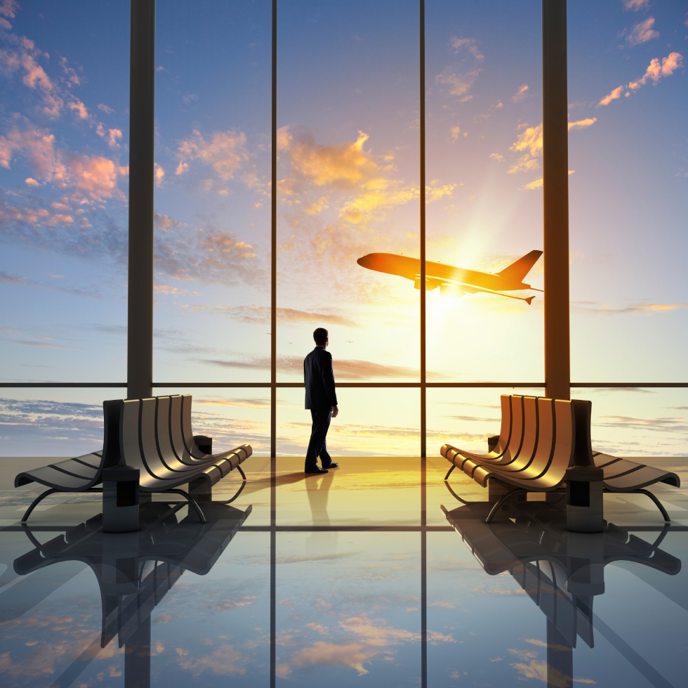 Businessman at airport looking airplane taking off. Credit: istock