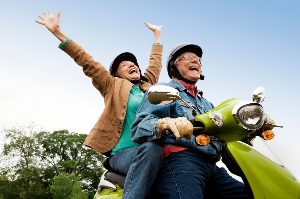 Senior couple riding motor scooter having fun. Credit: istock