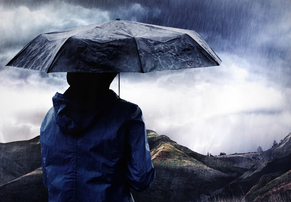 Shot of a woman covered with an umbrella watching a thunderstorm over a mountain