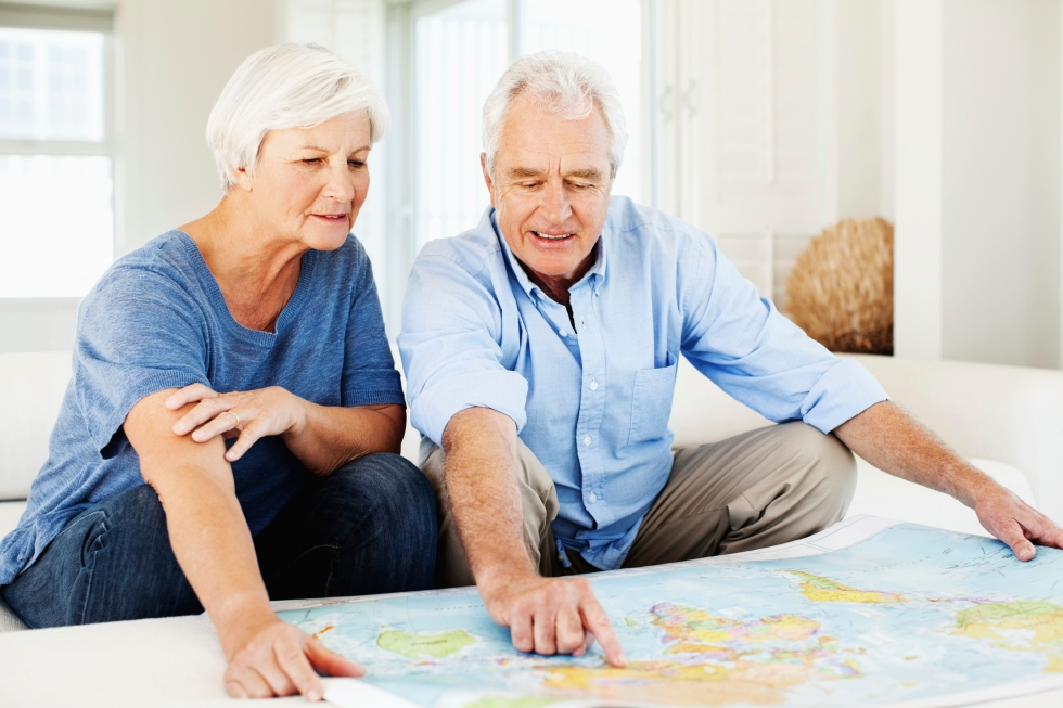 Senior woman with senior man pointing at world map while planning for vacation at home. Horizontal shot.