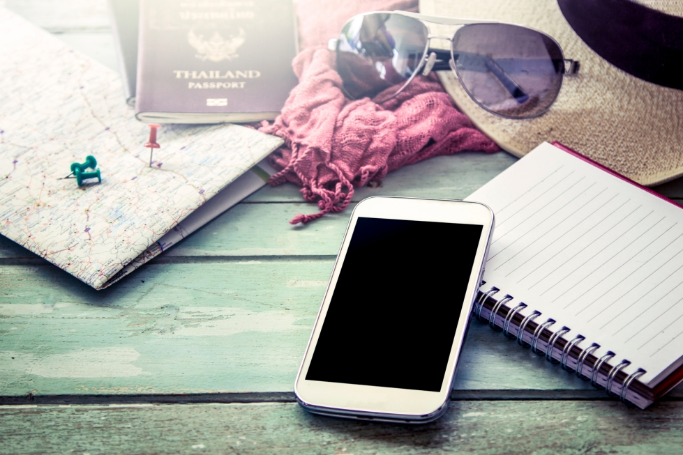 Preparation for travel, cellphone, sunglasses ,passport, road map,hat and notebook on wooden table in vintage filter