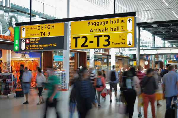 A busy airport terminal with many blurred moving people and a yellow and black sign directing to the baggage and arrivals hall.